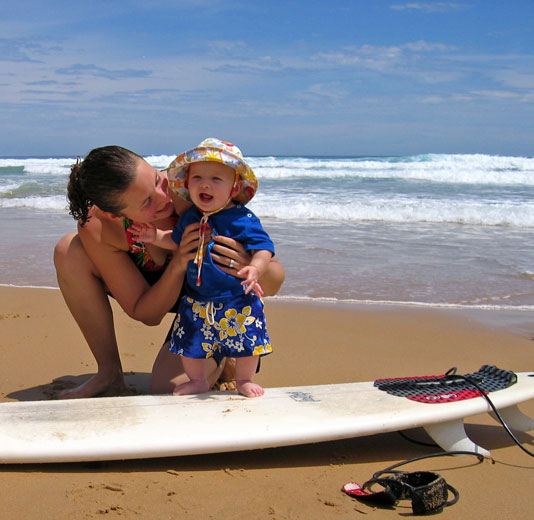 Mother and Son on the beach with a surfboard