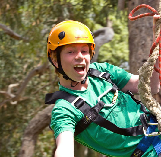 Happy Boy in yellow helmet on Flying Fox
