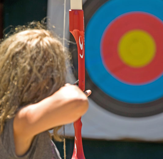Archery Target inthe background, girl pulling an arrow through the bow