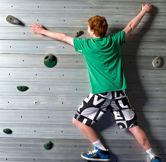 Redheaded Boy in Green Shirt on the Traversing Wall