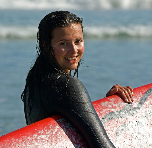 Smiling Surfer Girl with Red Surfboard